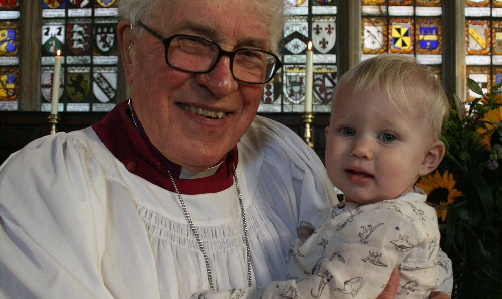 A Bishop and proud grandfather baptises his grandson