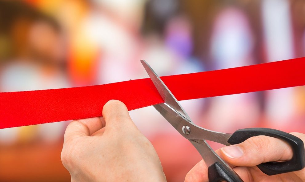 Hand with scissors cutting red ribbon