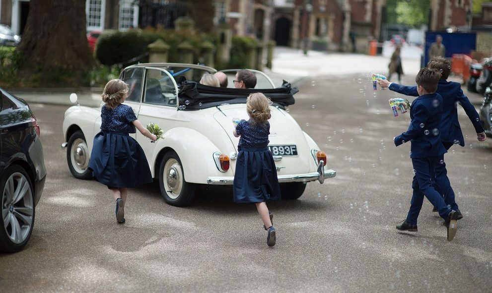 Children chasing after a wedding car at Lincoln's Inn