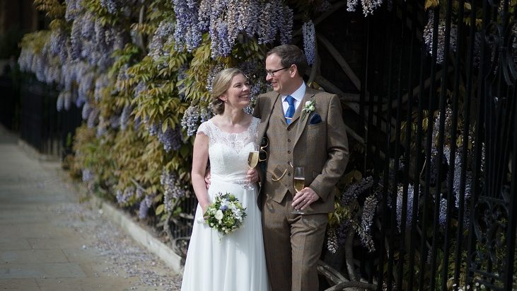A wedding couple standing underneath wisteria