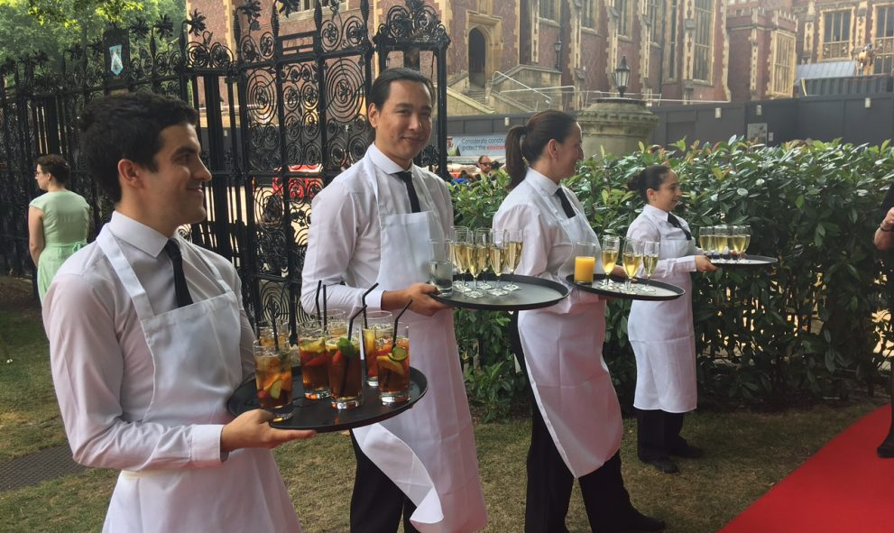waiting staff serving drinks on red carpet in New Square