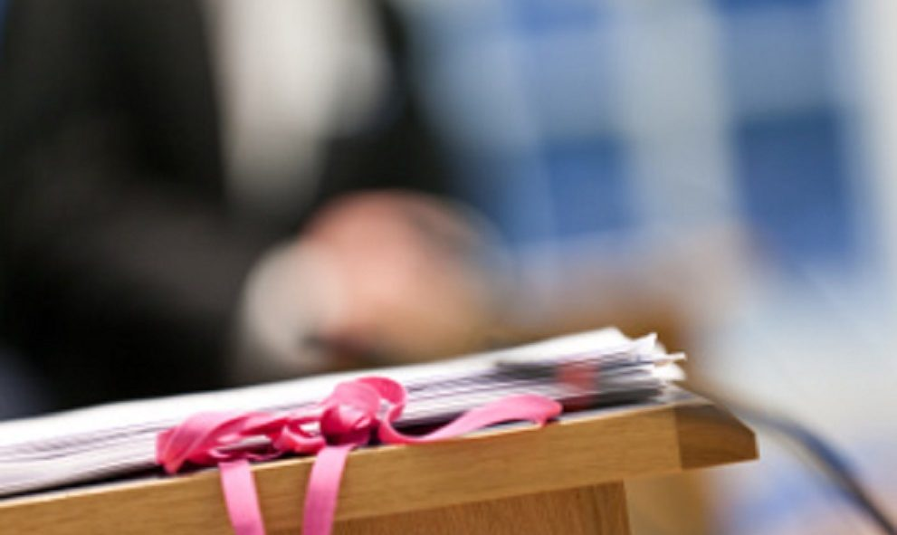 legal documents in foreground with blurred person in barrister attire in background
