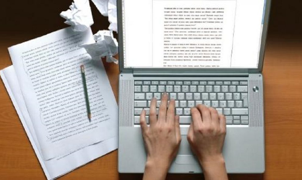 hands on laptop with papers at side - image representing essay writing